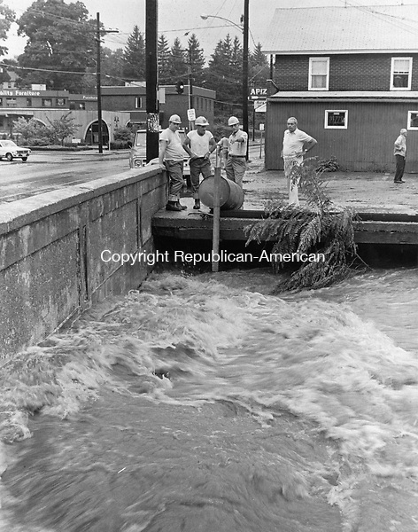 Rushing Waters of the rain-swollen Steele Brook dash against the Oakville bridge during the flood of 1975.