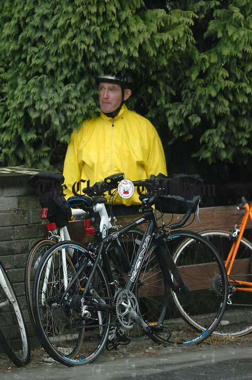 Tommy Haugh from Coolmeen takes shelter from a thunderstorm at Ogonnolloe during the Clare 250 mile cycle. Photograph by John Kelly.