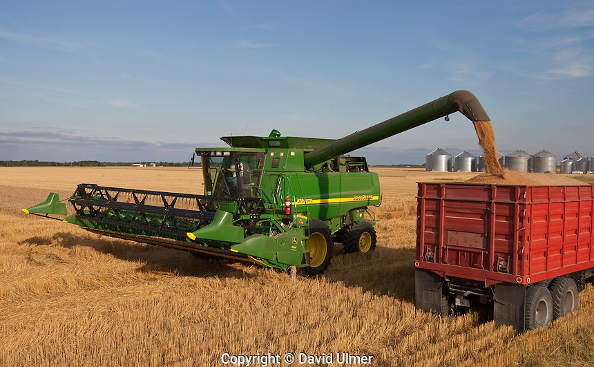 John Deere combine dumps wheat into grain truck for transport to storage.
