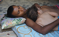 men sleeping with baby in arms