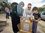 Foza Othman, a refugee from Aleppo, Syria, inspects the contents of a box of household supplies outside a community center in Amman, Jordan. Othman, who is not allowed to work in Jordan, received the box from International Orthodox Christian Charities, a member of the ACT Alliance. Fadi Wakileh, an aid worker for IOCC, and one of her sons helps her.