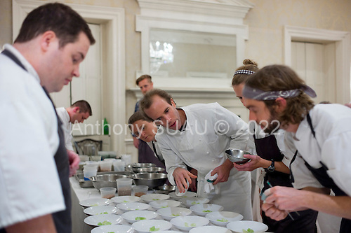 Charleston, South Carolina<br /> October 24, 2013<br /> <br /> 17 internationally renowned chefs, attending the Cook It Raw event in Charleston, put the final touches on plates and serve them to a select crowd for dinner at McCrady's restaurant.<br /> <br /> Chef Dan Barber, (center) from restaurant Blue Hill at Stone Barns, New York, gives a few instructions about his plate to helpers. Behind him is chef April Bloomfield from the restaurant, The Spotted Pig, New York City.