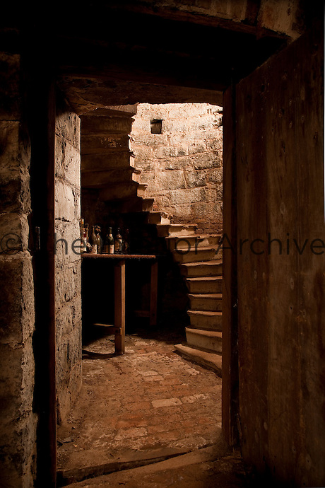 Steps wind down to the wine cellar in the depths of the original castle