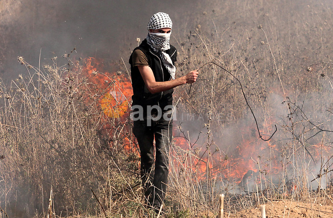 A Palestinian protester burns tires during clashes with Israeli security forces near the border fence between Israel and the Gaza Strip on October 9, 2015 east of Gaza City. Tension and protests rose after an Israeli man on 09 October stabbed four Palestinians in southern Israel, in what is being seen as a revenge attack, officials said. On 08 October several violent incidents happened, including stabbings which left eight Israelis injured, one Palestinian was killed in East Jerusalem and six in the Gaza Strip in clashes with the army while at least six were injured on the West Bank . Photo by Ashraf Amra