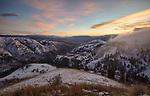 Idaho, North Central, Idaho County, Grangeville, White bird.  Evening fog rolls off White Bird Summit into the valley at sunset in winter.
