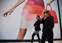 Passers by walk past an advertising hoarding placed in front of the the Fendi luxury leather goods store, Hong Kong, China, 07 March 2014. Hong Kong is known as a shopping mecca for luxury goods due to the fact that such goods are sold tax free in the ex-British colony, in contrast to mainland China where high taxes are still slapped on luxury goods.