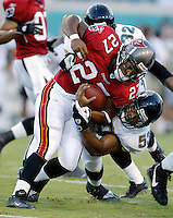Jacksonville Jaguar linebacker T.J. Slaughter (#53) tackles Tampa Bay Buccaneer running back Aaron Stecker during an NFL preseason game in Jacksonville, FL on Friday, August 15, 2002.  Tampa bay won the game 20 to 0. (Photo by Brian Cleary/ www.bcpix.com )