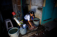 "15 year old Nasridah, a student at Kartini Emergency School, washes clothes in the slum neigbourhood where she lives. Unable to continue her studies in her village due to economic constraints, Nasridah came to Jakarta in early 2007 to work as a domestic worker. She says, ""One day while I was watching the television, I saw news about the 'Twin Teachers' and their free emergency school. I was very excited and decided to look for the school. Upon meeting the twins I asked them if I could study there and they accepted me. Because I don't have a home in Jakarta, the twins found me a family in the slum area near the school who were willing to let me stay in their home for free in exchange for some household chores such as washing and ironing clothes. When I complete my high school study I would like to work in a Salon."" Since the early 1990s, twin sisters Sri Rosyati (known as Rossy) and Sri Irianingsih (known as Rian) have used their family inheritance to set up and run 64 schools in different parts of Indonesia, providing primary education combined with practical skills to some of the country's most deprived children."