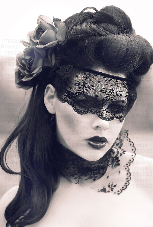 face of a mysterious and pretty young woman with dark hair and a lace blindfold over her eyes