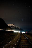 Vehicles travel Turnagain Arm at night between Anchorage and Girdwood on Alaska Route 1.