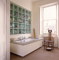 In this bathroom the wall space above the bath is used to display a collection of semi-precious stones and minerals housed in custom-made glass cases