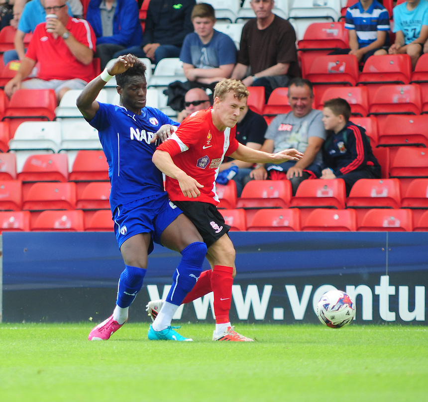 Chesterfield's Armand Gnawduellet vies for possession with Lincoln City's Tom Miller<br /> <br /> Photographer Chris Vaughan/CameraSport<br /> <br /> Football - Friendly - Lincoln City v Chesterfield - Saturday 19th July 2014 - Sincil Bank Stadium - Lincoln<br /> <br /> &copy; CameraSport - 43 Linden Ave. Countesthorpe. Leicester. England. LE8 5PG - Tel: +44 (0) 116 277 4147 - admin@camerasport.com - www.camerasport.com