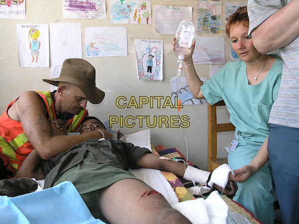 Volunteer ?DONNY? from Australia helps out with one of the wounded in the aftermath of the deadly tsunami in Sri Lanka .in The Third Wave.*Filmstill - Editorial Use Only*.CAP/PLF.Supplied by Capital Pictures.
