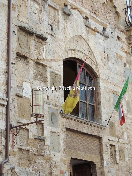 San Gimignano, Italy - October 4, 2012:  Flags flank an upper window of the Palazzo Comunale.