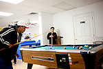 Eduardo Barajas  watches his father Roberto play pool as the two wait for clothes to dry at Coin Laundry in East Point, Georgia December 30, 2009. Monica, Eduardo's mother, has been separated from her husband and son so she could continue dialysis in Mexico.