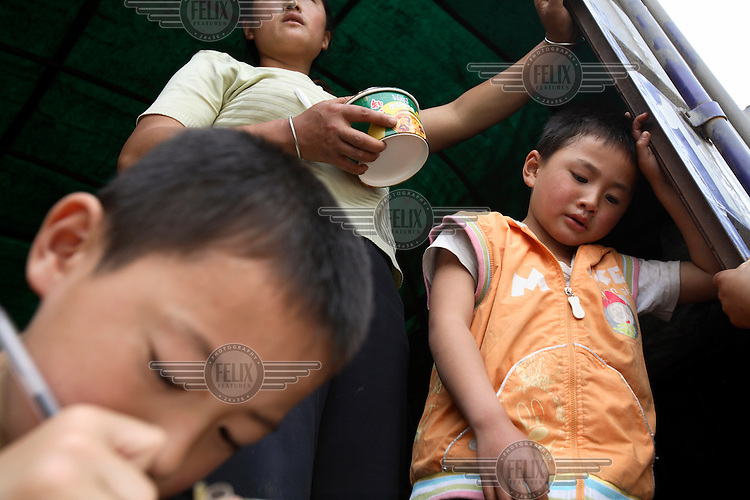 Six year old Li Yue in a makeshift home inside a truck at the Jiuzhou Stadium in Mianyang. On the 12/05/2008 an earthquake measuring 8.0 on the Richter scale hit the province of Sichuan.