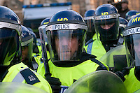 Police wear riot gear as they protect the Houses of Parliament during a student demonstration in Westminster, central London on the day the government passed a bill to increase university tuition fees.