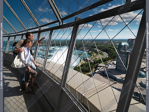 Young tourist couple enjoying view from Skylon tower at Niagara Falls, Ontario, Canada.