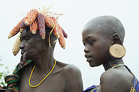 "Ethiopia. Southern Nations, Nationalities, and Peoples' Region. Omo Valley. Mursi tribe. Village and huts. Agro-pastoralist group. Nomadic. Two Mursi women. An elderly woman with maize on her head and  a teen women with a wooden earring. Mursi women are known as ""disk-lip"" women. The bottom lip is slit along its full length and the front bottom row of teeth are pulled out to accomodate the ceramic disk which is handmade with a rim around which the stretched lip is pulled. The women are famed for wearing large plates in their lips (round clay plates placed into a cut in the lower lip) and ears. The disk is seen as a symbol of beauty and wealth, and often the younger girls will pierce and strech their ear-lobes, inserting a matching disk in the extended lobe. The Omo Valley, situated in Africa's Great Rift Valley, is home to an estimated 200,000 indigenous peoples who have lived there for millennia. Amongst them are 8'000 Mursi who dwell between the Omo and Mago rivers. Southern Nations, Nationalities, and Peoples' Region (often abbreviated as SNNPR) is one of the nine ethnic divisions of Ethiopia. 11.11.15 © 2015 Didier Ruef"