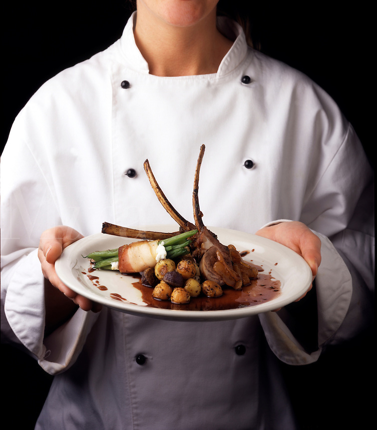 A Lady Chef Holding Roasted Rack of Lamb Entree with apricot port glaze