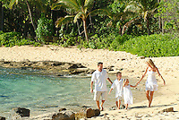 Family of four walking the beach while on vacation in Hawaii