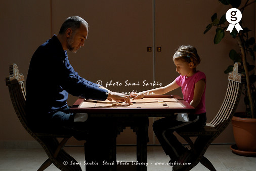 Father and daughter (5-7) playing 'Carrom' board game, profile (Licence this image exclusively with Getty: http://www.gettyimages.com/detail/73532507 )