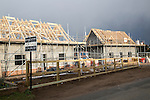 New houses under construction in the village of Bawdsey, Suffolk, England, UK dark storm clouds overhead