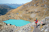 Trail running above milky turquoise water on the Pizol 5 Lakes trail above Sargans, in eastern Switzerland
