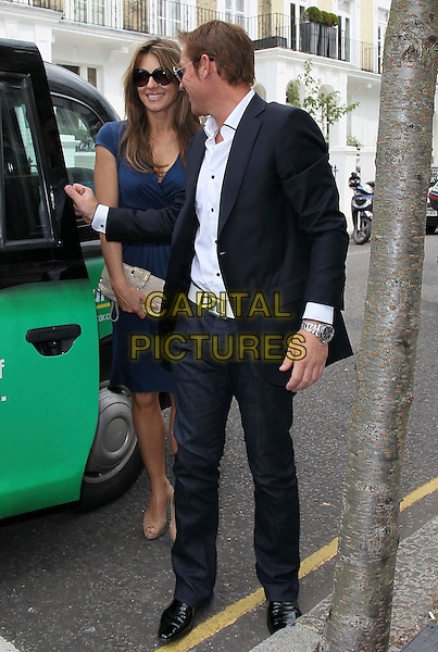 "Elizbaeth ""Liz"" Hurley & Shane Warne.Seen going for lunch in Chelsea, London, England, UK, .June 24th 2011..full length navy dress clutch bag beige shoes  sunglasses shirt black jacket blazer jeans  blue white taxi cab couple .CAP/HIL.©John Hillcoat/Capital Pictures."