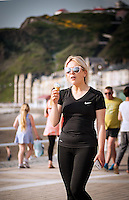 UK Weather: Aberystwyth, Ceredigion, West Wales <br /> A woman enjoys an icecream as she walks along the seafront