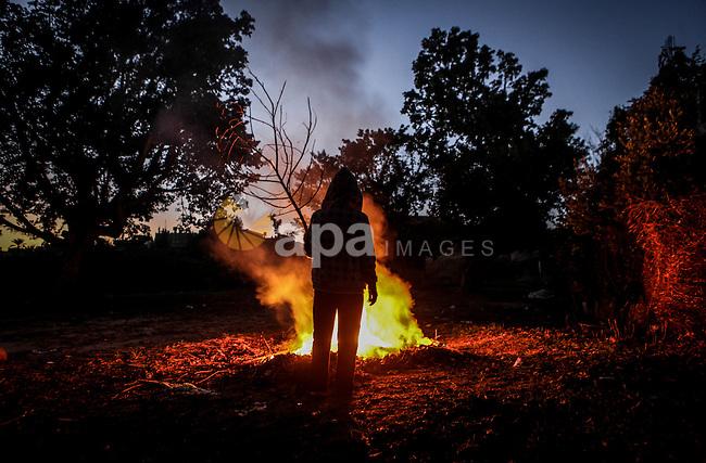 A Palestinian boy warm himself up by a firewood in Beit Lahia, northern Gaza Strip, 23 December 2013. Photo by Ezz Zanoun