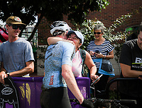 NWA Democrat-Gazette/CHARLIE KAIJO Angie Vrouwenvelder (center right) hugs Luke Vrouwenvelder of Chapel Hill, NC. who placed second in the men's race of the Epic Rides Oz Trails championship mountain bike race, Sunday, October 7, 2018 at the downtown square in Bentonville.<br />