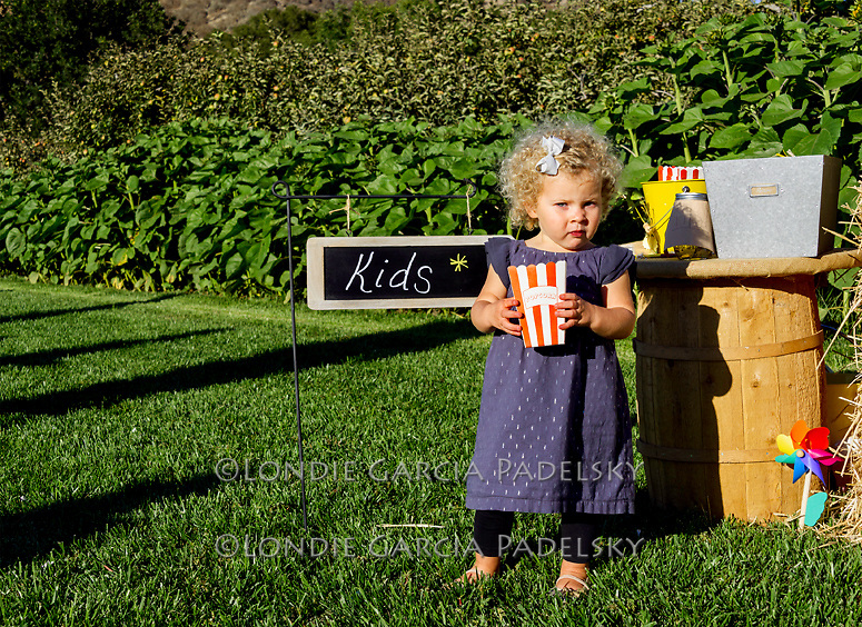 Little girl gets some popcorn at an event at Avila Valley Barn