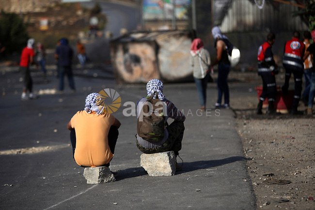 Palestinian protesters sit on the road during clashes with Israeli security forces near the Jewish settlement of Bet El, near the West Bank city of Ramallah, on October 14, 2015. Seven Israelis and 30 Palestinians, including children and assailants, have been killed in two weeks of bloodshed in Israel, Jerusalem and the occupied West Bank. The violence has been partly triggered by Palestinians' anger over what they see as increased Jewish encroachment on Jerusalem's Al-Aqsa mosque compound. Photo by Shadi Hatem