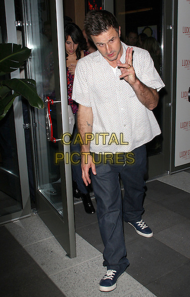 DAVID ARQUETTE.Grand Opening of Lucky Strike Lane and Lounge held at Lucky Strike LA, Los Angeles, California, USA, .21 November 2008..full length white print shirt jeans trainers shoes  sneakers hand gesture funny.CAP/ADM/KB.©Kevan Brooks/Admedia/Capital PIctures
