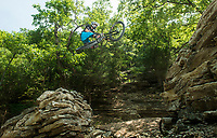 NWA Democrat-Gazette/BEN GOFF @NWABENGOFF<br /> Gary Vernon of Bella Vista, a program officer with the Walton Family Foundation, rides one of the larger gap jumps Thursday, June 14, 2018, during a grand opening for new downhill mountain bike trails at Lake Leatherwood City Park in Eureka Springs. The Walton Family Foundation and Eureka Springs Parks and Recreation Commission partnered to build the new downhills trails at the park already known for it's extensive network of singletrack. Many of the new trails, built by Rock Solid Trail Contracting, include large, expert-level drops, jumps and technical rock features. Over the next 60 days, the Eureka Springs Parks and Recreation Commission will be funding free shuttles operated by Adventure Mountain Outfitters and Phat Tire Bike Shop for riders on most Thursdays and Fridays. Justin Huss, director of the commission, advises visitors to call the park to check on shuttle schedules before visiting. Huss says after the initial 60 days, the shuttle services will be offered on busy days with the purchase of a pass.