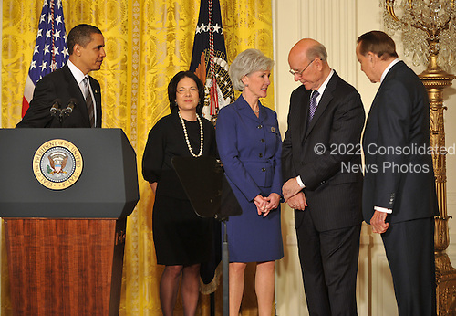 """Washington, D.C. - March 2, 2009 -- United States Senator Pat Roberts (Republican of Kansas), 2nd right, shares some thoughts with Governor Kathleen Sebelius (Democrat of Kansas), center, after United States President Barack Obama, left, made remarks naming Governor Sebelius as Secretary of the Department of Health and Human Services (HHS) in the East Room of the White House in Washington, DC on Monday, March 2, 2009.  The President also announced the release of $155 million authorized by the American Recovery and Reinvestment Act (ARRA) that will support 126 new health centers.  In a release, the White House stated """"These health centers will help people in need - many with no health insurance - obtain access to comprehensive primary and preventive health care services.""""   From left to right: President Obama; Governor Sebelius; Nancy-Ann DeParle, just named Counselor to the President and Director of the White House Office for Health Reform;  Senator Roberts; and Former United States Senator Bob Dole (Republican of Kansas)..Credit: Ron Sachs / Pool via CNP"""