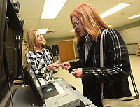 """NWA Democrat-Gazette/FLIP PUTTHOFF <br />Sharon Rose (left) with the Benton County Election Commission hands Stephanie Blevins an """"I voted"""" sticker after Blevins cast her ballot Tuesday Dec. 4 2018 at Bentonville Church of Christ in the Bentonville mayoral election."""
