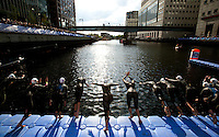 30 JUN 2011 - LONDON, GBR - Competitors dive into the water for the start of the women's super sprint elimination round at the GE Canary Wharf Triathlon (PHOTO (C) NIGEL FARROW)