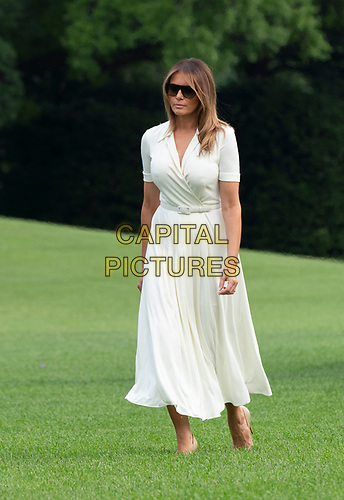 First lady Melania Trump walks on the South Lawn as she and United States President Donald J. Trump return to the White House in Washington, DC after spending a weekend at their residence in Bedminster, New  Jersey on Sunday, July 7, 2019.<br /> CAP/MPI/RS<br /> ©RS/MPI/Capital Pictures