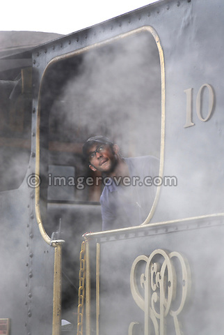 Engine driver looking out of a historic steam train at Paranapiacaba station; near Sao Paulo, Brazil. In 1856 the British-owned Sao Paulo Railway Company was awarded the concession to operate a rail line between the port of Santos and Jundai, 70km north of Sao Paulo city, in what was then a developing coffee-growing region. The 139km line was completed in 1867, remaining under British control until 1947. Overcoming the near-vertical incline of the Serra do Mar that separates the interior of the state from the coast, the line was using the largest funicular system in the world and was regarded as an engineering miracle. --- No releases available.