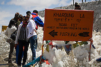 Tourists pose for photos in front of signboards as they stop on the top of the Khardung La (Pass) at 5602m in the Nubra Valley, Ladakh on 4th June 2009.  The valley of Ladakh is located in the Indian Himalayas, in the northern state of Jammu and Kashmir. Photo by Suzanne Lee