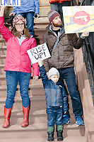 "A family holds signs, including one reading ""Rise up!"" from a stoop while People take part in the March For Our Lives protest, walking from Roxbury Crossing to Boston Common, in Boston, Massachusetts, USA, on Sat., March 24, 2018, in response to recent school gun violence."