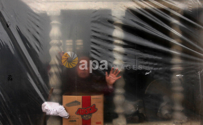 A Palestinian woman looks through her dwelling covered with plastic sheet in Khan Younis in the southern Gaza Strip December 19, 2016. Photo by Ashraf Amra