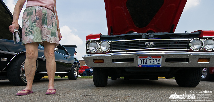 An older woman stands at a row of older cars at a hot rod car show