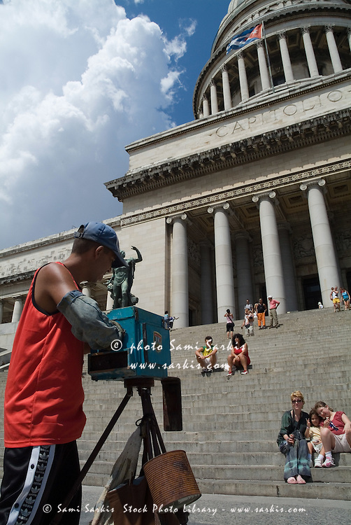 Tourists having their photo taken outside the El Capitolio (National Capitol) building in Havana, Cuba.