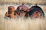 Idaho, Southeast, Aberdeen. A old red tractor in tall grasses in mid winter.