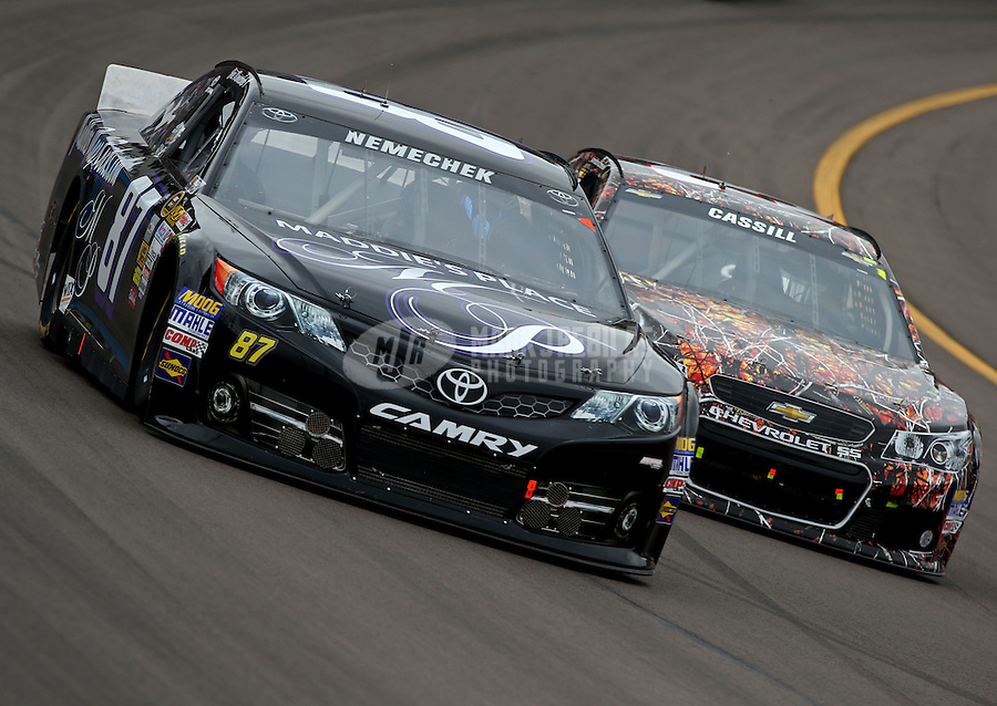 Mar. 3, 2013; Avondale, AZ, USA; NASCAR Sprint Cup Series driver Joe Nemechek (left) races alongside Landon Cassill during the Subway Fresh Fit 500 at Phoenix International Raceway. Mandatory Credit: Mark J. Rebilas-