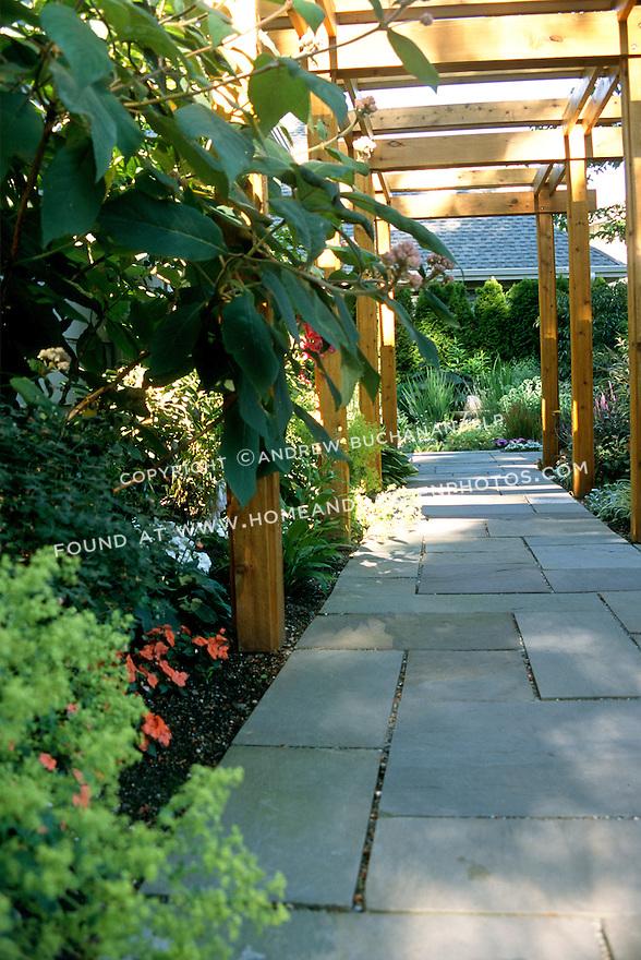 An arbor-covered flagstone walkway leads through a lush summertime garden.