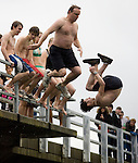 Kevin Dunn (L) takes a flying leap as leaps Austin Jackman  (R) performs a  front flip from a bridge into the Burley Lagoon in Olalla, Washington on 1 January  2010. Over 300 hardy participants  braved the chilly lagoon waters to join in on the annual New Year's Day Tradition. Jim Bryant Photo. ©2010. ALL RIGHTS RESERVED.